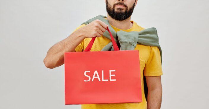 man holding a sale paper bag