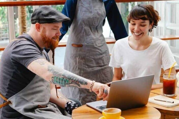 Cheerful Man and woman looking at laptop