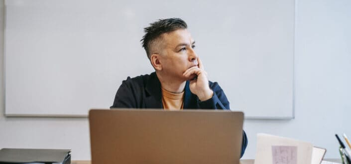 A mature man on a deep thought in front of his computer