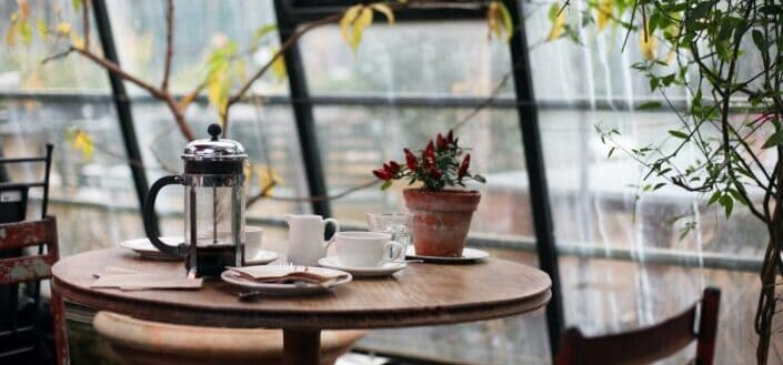 round brown wooden table with french press on top with white ceramic teacup beside