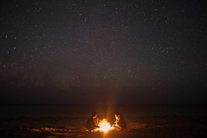 Couple sitting on the beach at night