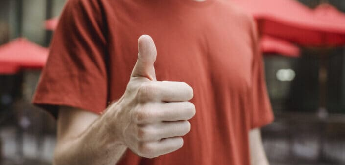 A man in a red shirt doing a thumbs up sign