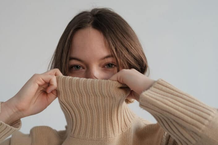 Woman covering her face with her turtle neck blouse