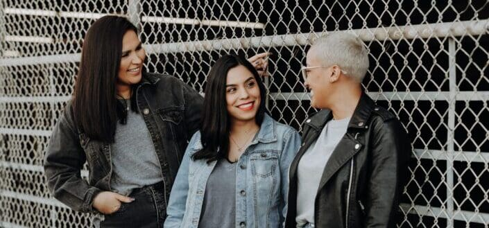 3 women standing beside gray metal fence