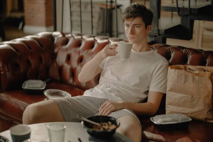 A guy having a breakfast on a couch.