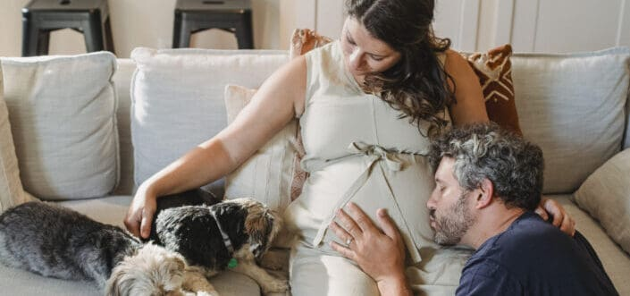 Happy pregnant couple with dogs on couch