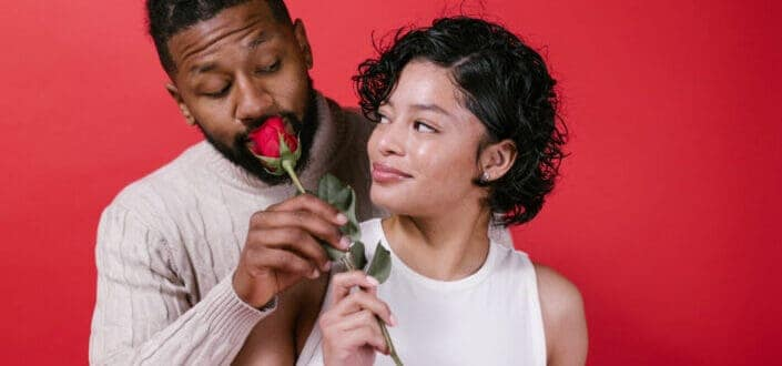 couple holding rose looking at each other