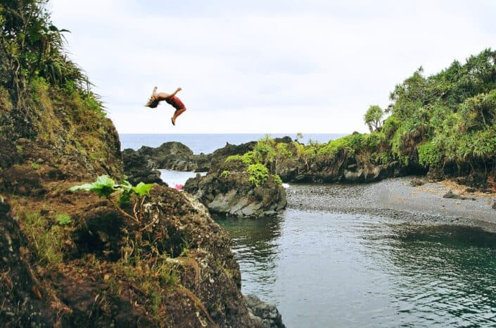 Man back-flipping from a cliff