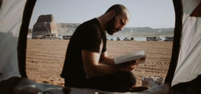 Person reading book outside his tent