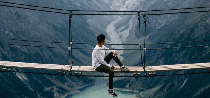 Man sitting on a hanging bridge