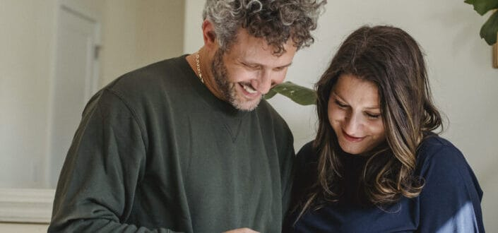 Happy pregnant couple sharing smartphone at home