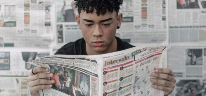 Concentrated ethnic man reading newspaper at home