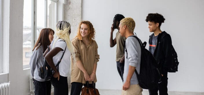 Diverse classmates talking to each other after studies