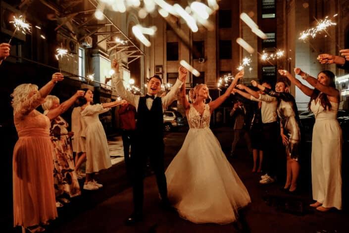 friends and newlywed couple celebrating wedding at night