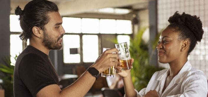 Man and Woman Clinking Two Drinking Glasses Filled With Beer
