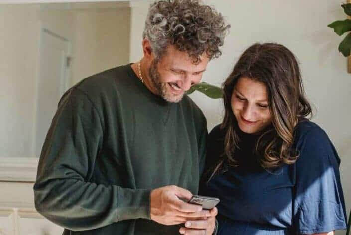 a couple smiling at a phone