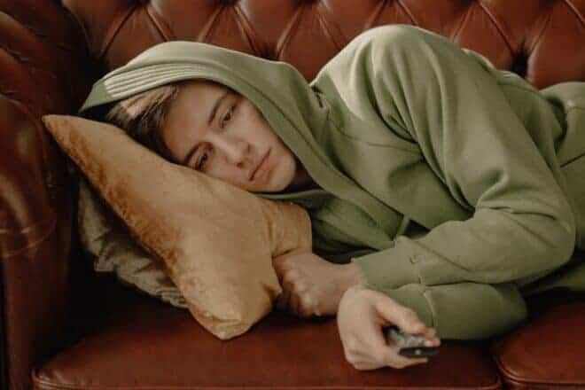Person in Gray Robe Lying on Leather Couch - alpha things to do when you're bored this lockdown