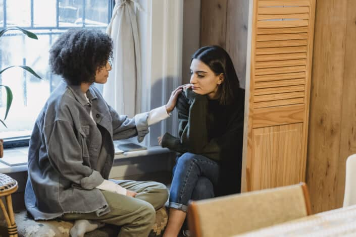 woman supporting upset female friend at home